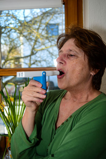 Woman inhaling with medical equipment while standing against window at home