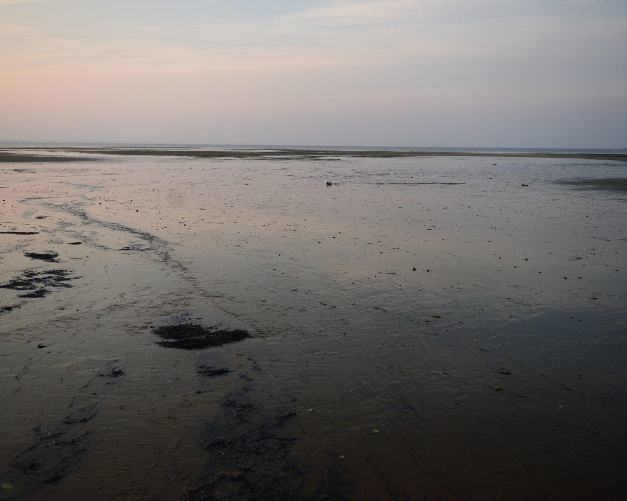Wet Shore Against Sunrise Sky