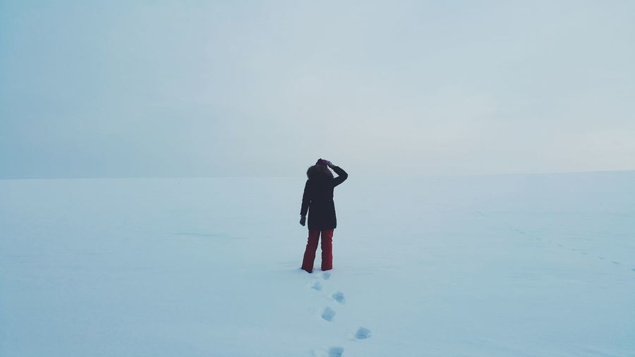 Rear View Of Person Standing On Snow Covered Field Against Sky