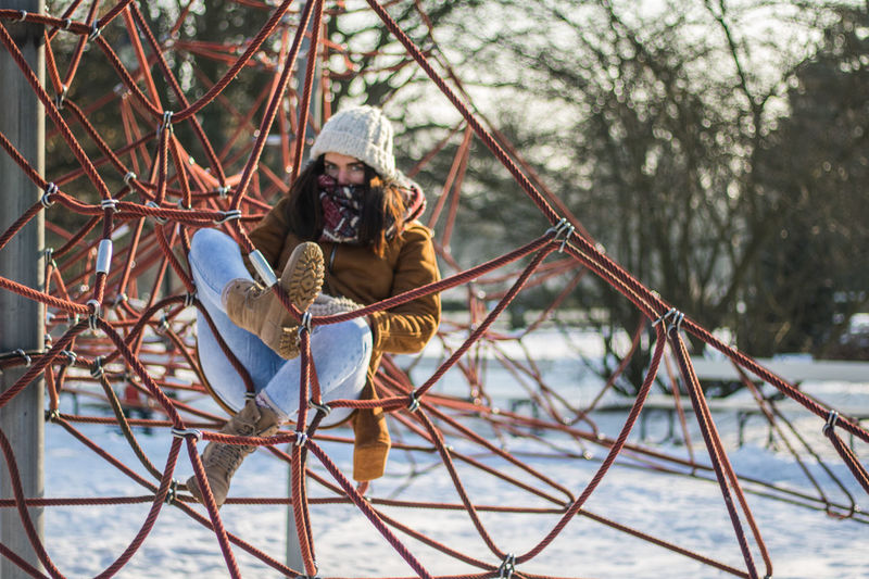 Full length portrait of woman resting on ropes at snow covered park