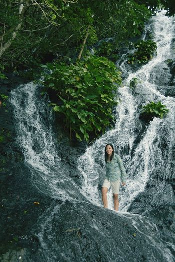 Woman standing against waterfall in forest