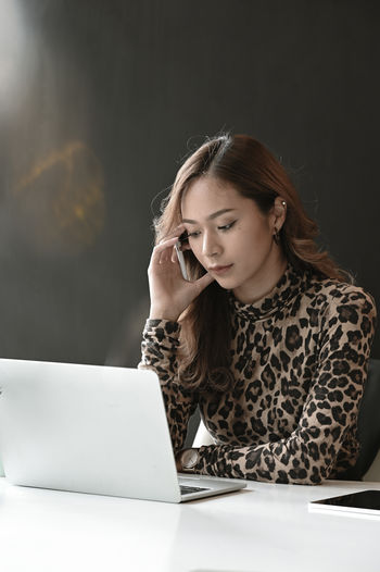 Young woman using laptop on desk while sitting in office