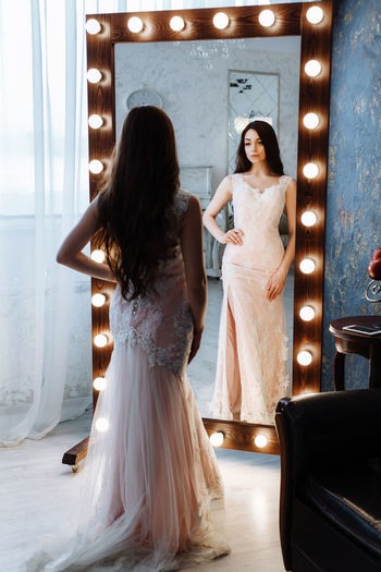 Rear view of bride standing in front of illuminated mirror