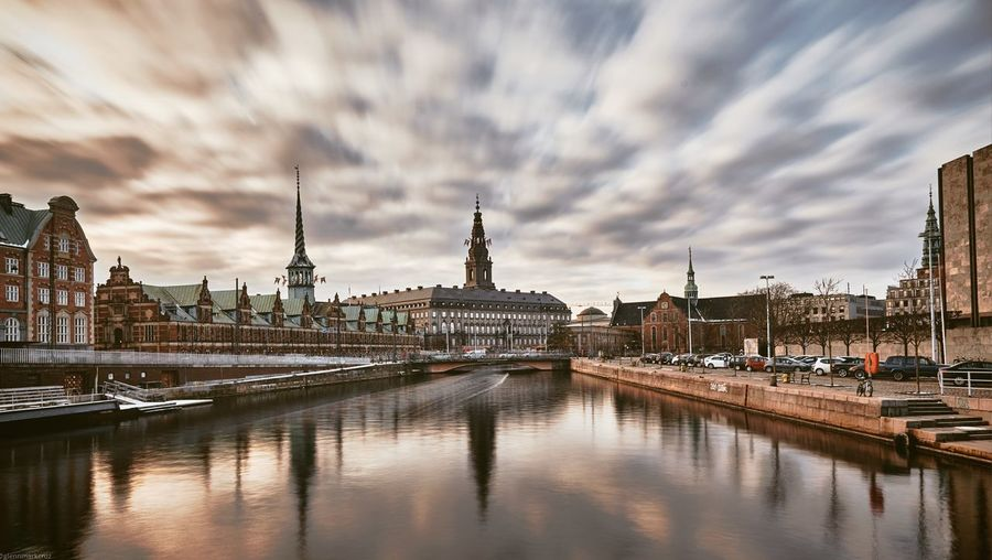 River and buildings in city against cloudy sky