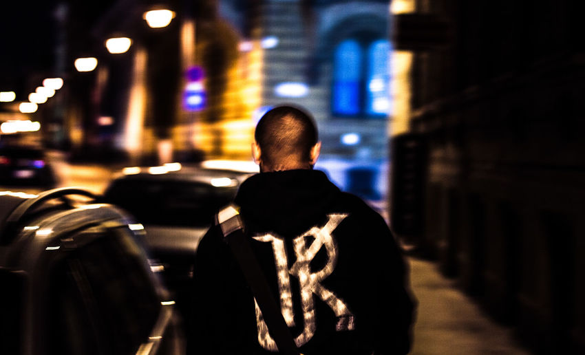 Rear view of man standing in illuminated city at night