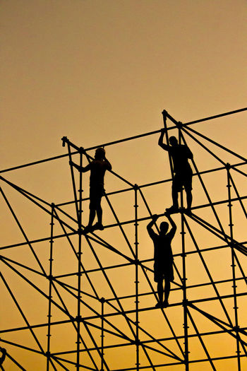 Low Angle View Of Silhouette Men Working On Construction Frame Against Orange Sky
