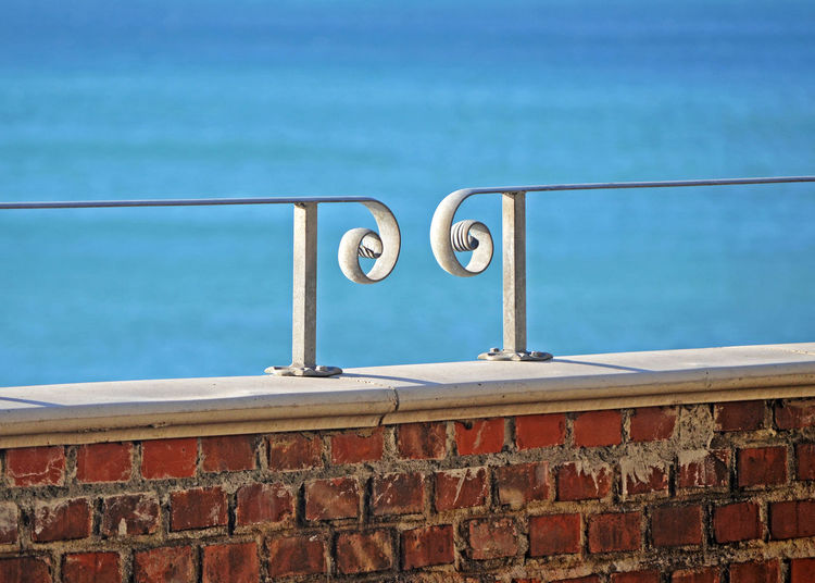 Close-up of railing against blue wall
