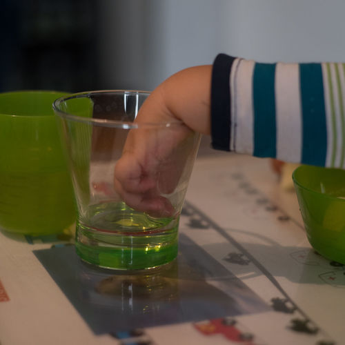 Frühkindliche Feinmotorik 1 Babyboy Close Up Colorful Drink Drinking Glass Finger Food And Drink Forearm Freshness G Green Color Gri Gripping Hand Holding Indoors  Part Of Person Refreshment Searching For Food Selective Focus Striped Pattern Table