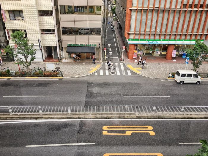 Vehicles on road by buildings in city