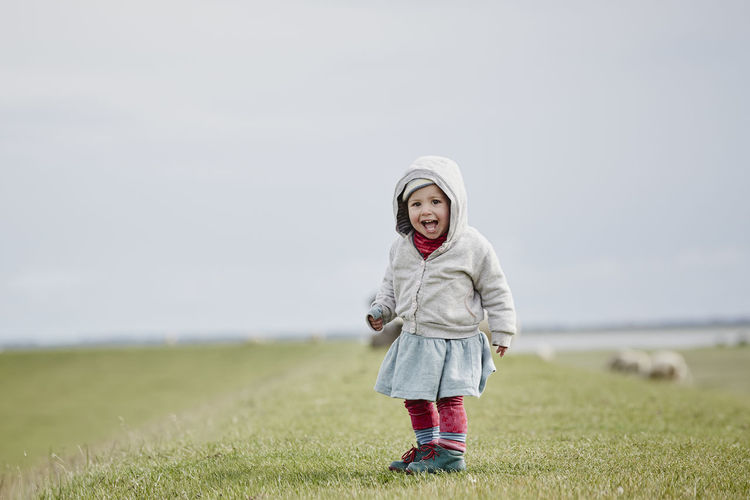 Full length of happy boy standing on field