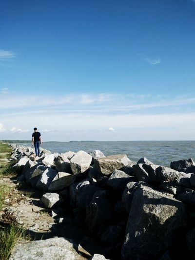 Rear View Of Man Standing On Rock Against Sea At Beach