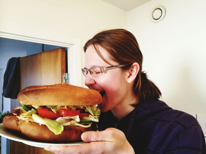 Woman holding plate with hamburger in kitchen at home