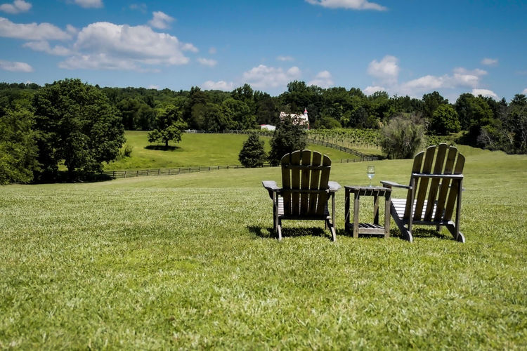 Empty chairs on grassy land against sky
