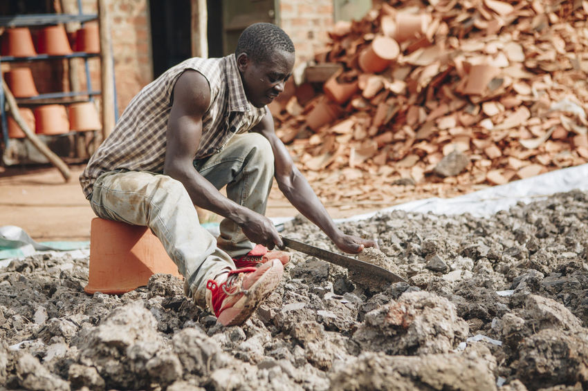 Africa African Breaking Business Ceramic Clay Dirty Factory Filter Hard Work Machete Manual Worker Manufacturing Men Men Only Mud Pottery Production Raw Material Social Business Warehouse Water Filter Worker Working Workshop