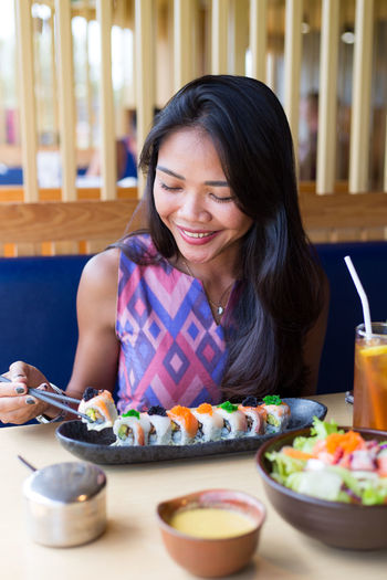 Happy Young Woman Having Sushi While Sitting At Restaurant