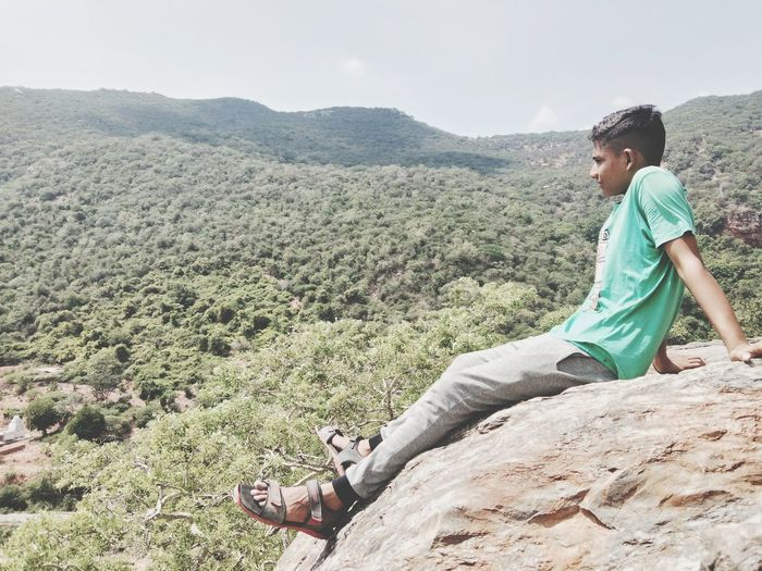 Side view of man relaxing on mountain
