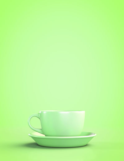 Close-up of coffee cup against green background