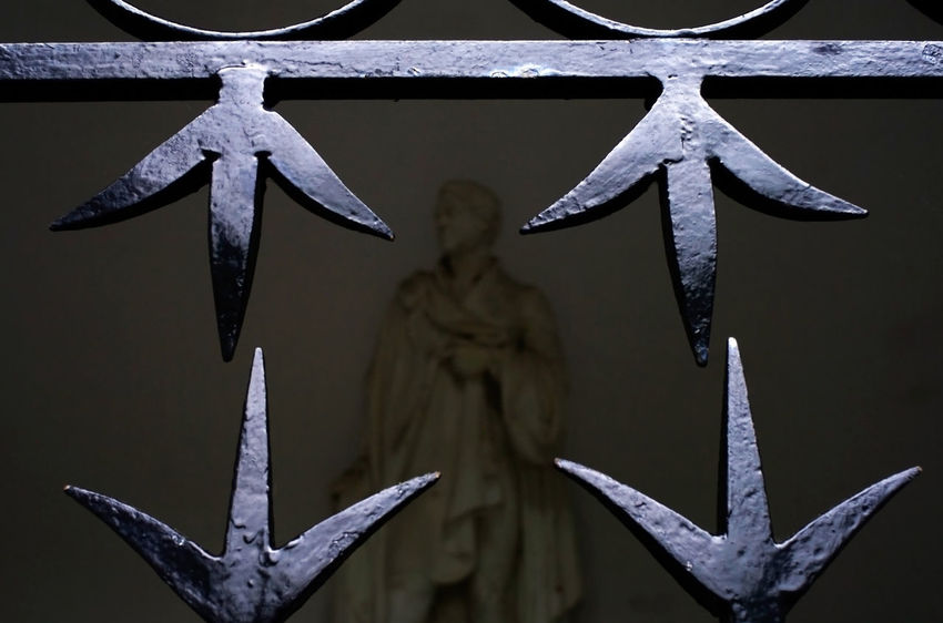 Close-up Day Detail Dim Light Focus On Foreground Framed Ironwork  Metal Outdoors Painted Black Pointed Railings Sharp Statue Victorian
