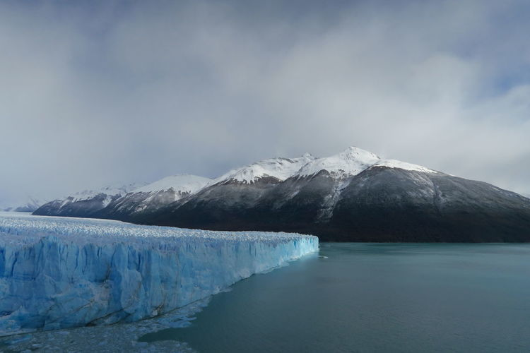 Scenic view of perito moreno glacier by lake against sky