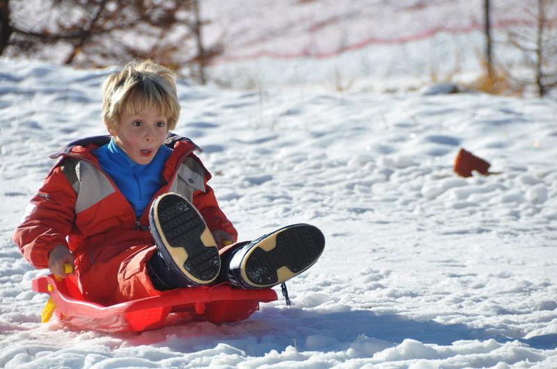 Boy tobogganing on snow