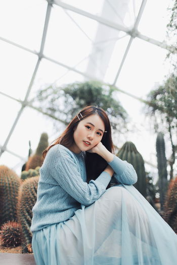 Portrait of young woman sitting against plants in greenhouse