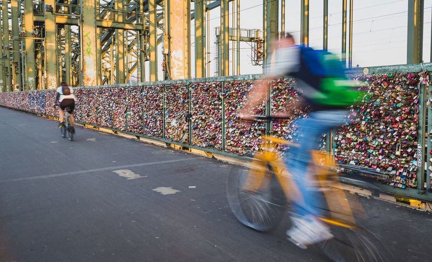Motion blurred cyclists passing walls of padlocks on the Hohenzollernbrücke (Hohenzollern Bridge) in Cologne, Germany Cologne Cologne , Köln,  Cyclist Köln Love Padlocks Travel Blurred Motion Bridge Cycling Famous Place Hohenzollern  Hohenzollernbrücke Love Lock Motion Multi Colored Padlock Padlocks On Bridge Real People Tourism Transportation Travel Destinations