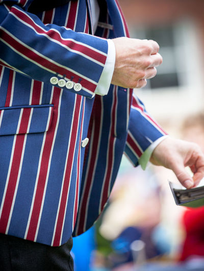 Midsection of man wearing striped blue and red jacket