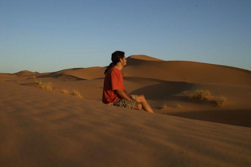 Man sitting on sand dune against clear sky at desert