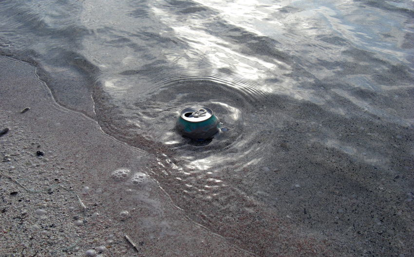 High angle view of abandoned drink can on shore