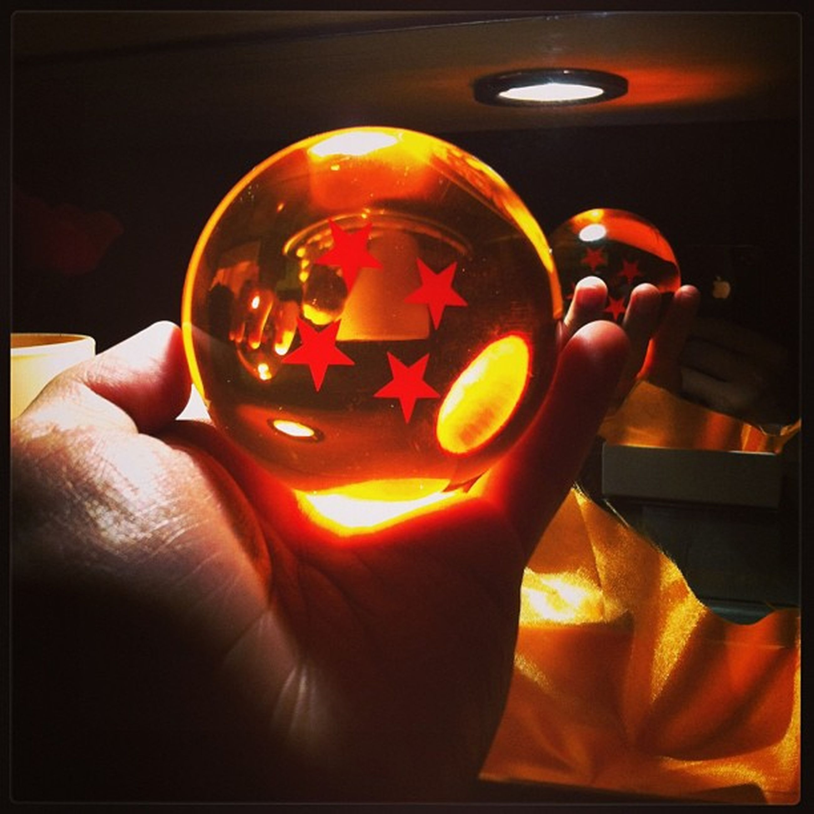 indoors, transfer print, person, auto post production filter, close-up, holding, part of, glass - material, human finger, unrecognizable person, reflection, illuminated, lifestyles, orange color, red, cropped, transparent