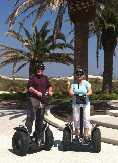 Beach Life Jekyll Island Arms Crossed Casual Clothing Crash Helmet Day Full Length Headwear Helmet Leisure Activity Looking At Camera Outdoors Palm Tree Portrait Road Segway Shadow Sports Helmet Standing Sunglasses Sunlight Sunny Transportation Tree Two People