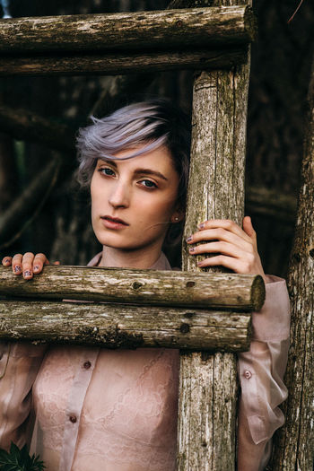 Feminine  Beautiful Woman Day Femininity Fence Focus On Foreground Front View Lifestyles Looking At Camera One Person Portrait Purple Hair Real People Women Wood - Material Young Adult Young Women