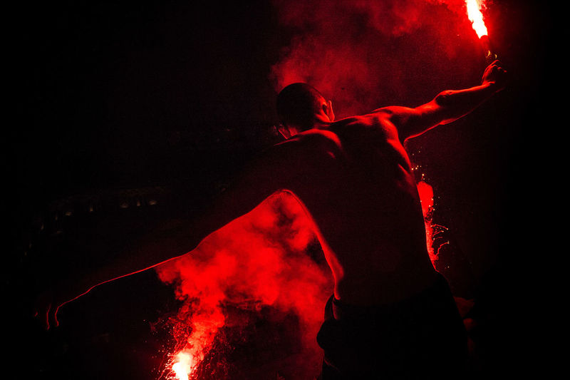 Rear View Of Shirtless Male Performer Holding Red Distress Flares