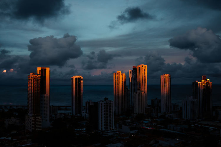Buildings in city against sky at dusk