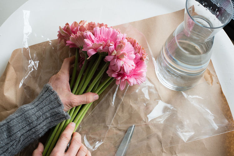Cropped hand of woman holding pink gerberas by vase at table