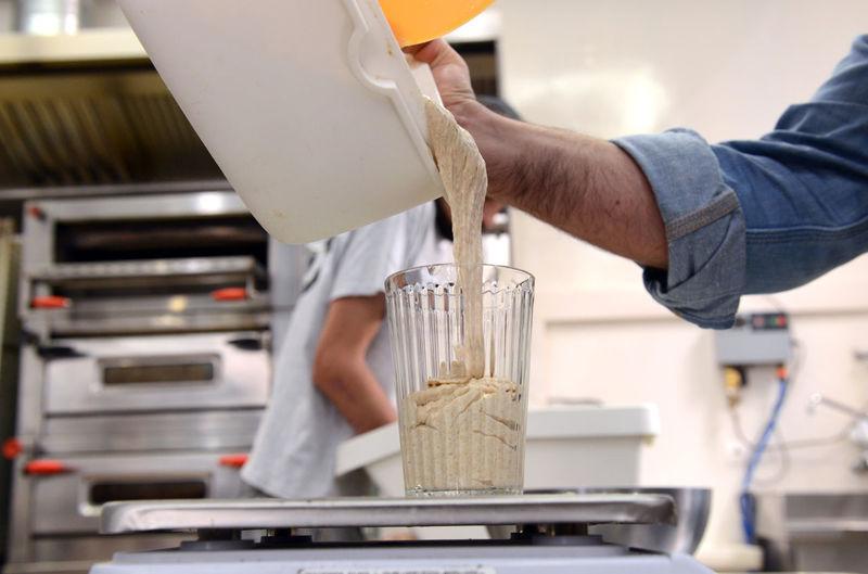 Cropped hand of man preparing food in factory