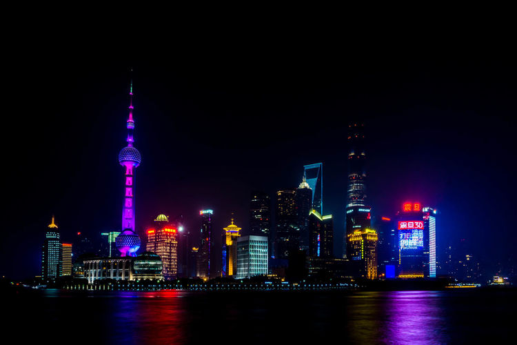 Illuminated Cityscape By Huangpu River Against Sky At Night