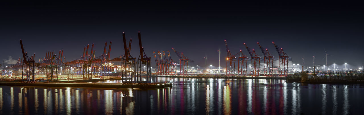 Illuminated commercial dock against clear sky at night