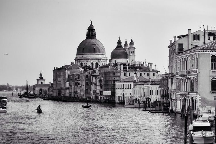 Boats in grand canal with santa maria della salute against sky