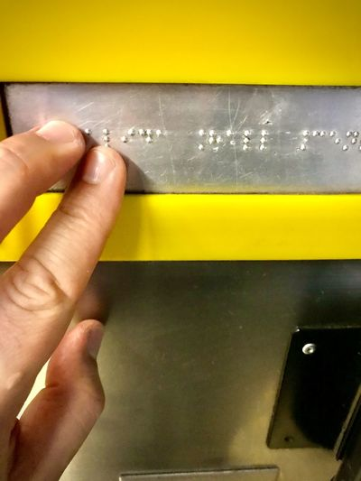 Close-up of hand holding yellow paper