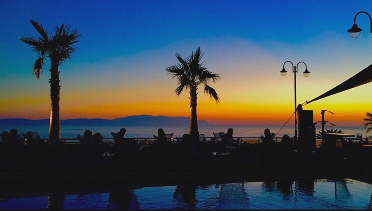 sunset, palm tree, silhouette, beauty in nature, sea, water, nature, tree, scenics, tranquility, sky, tranquil scene, swimming pool, beach, outdoors, vacations, horizon over water, people