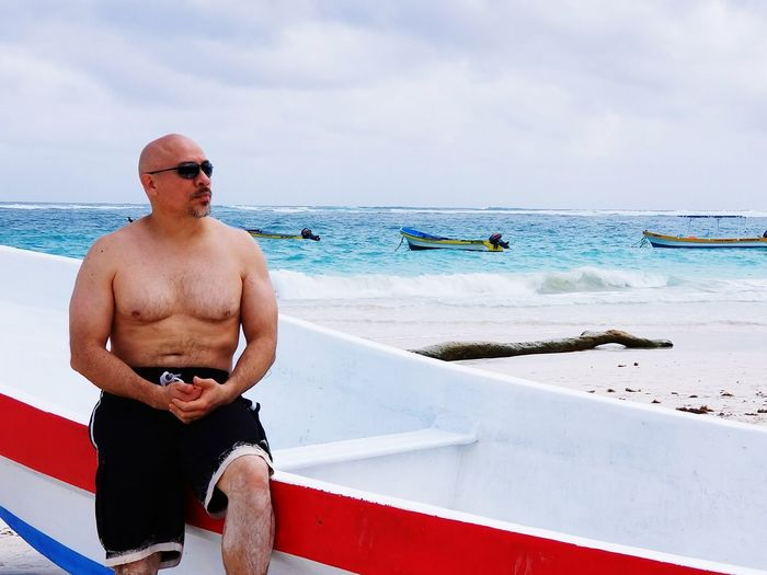 Man Sitting On Boat At Beach Against Sky