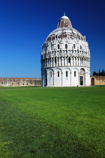 Grassy field by pisa baptistery against clear blue sky