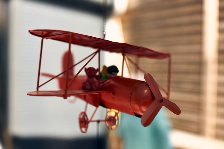 Close-up of toy flying hanging from airplane