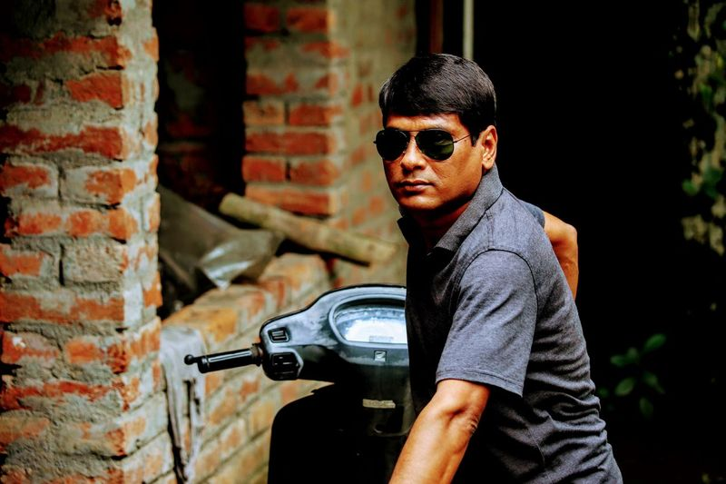 Man in sunglasses with motor scooter by brick wall