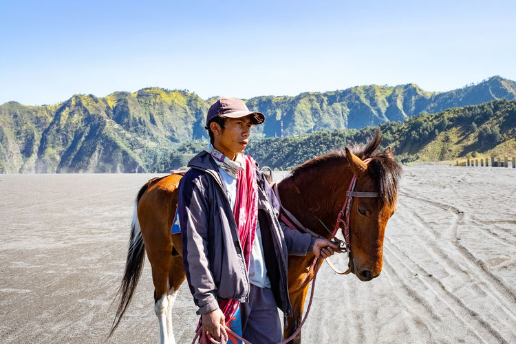 Man standing with horse on land against mountain range