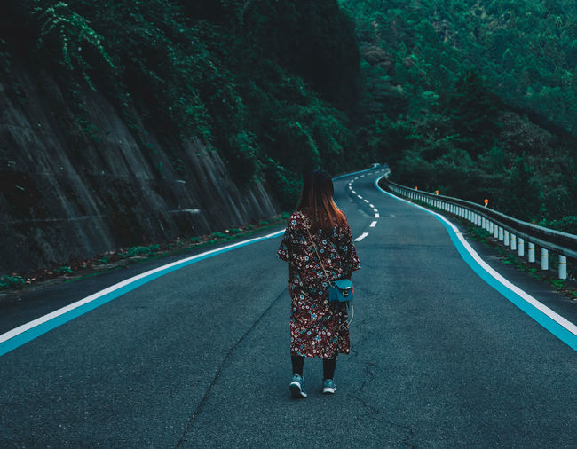 Rear view of woman standing on road amidst trees