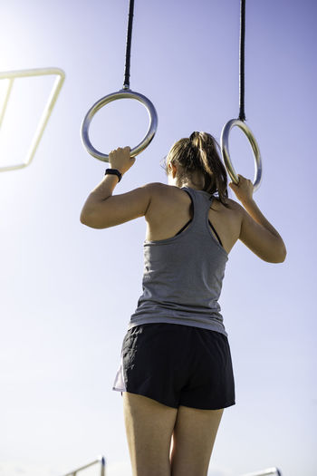 Rear view of woman exercising against sky