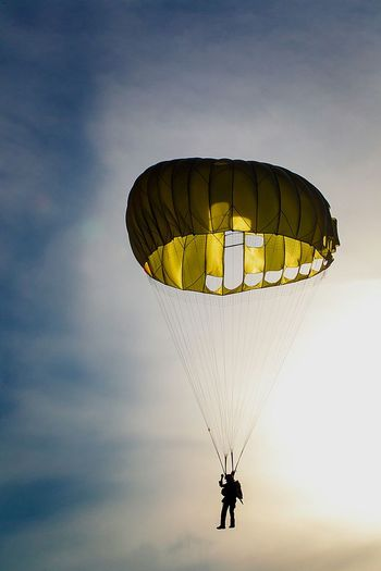 Silhouette of person parachuting against sky