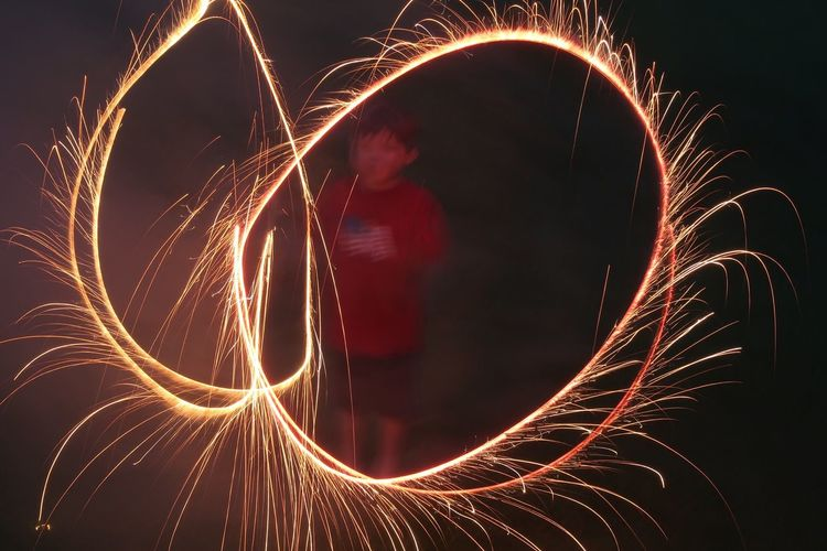 Boy performing light painting at night
